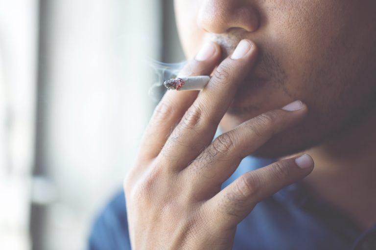 男性がたばこを吸っている