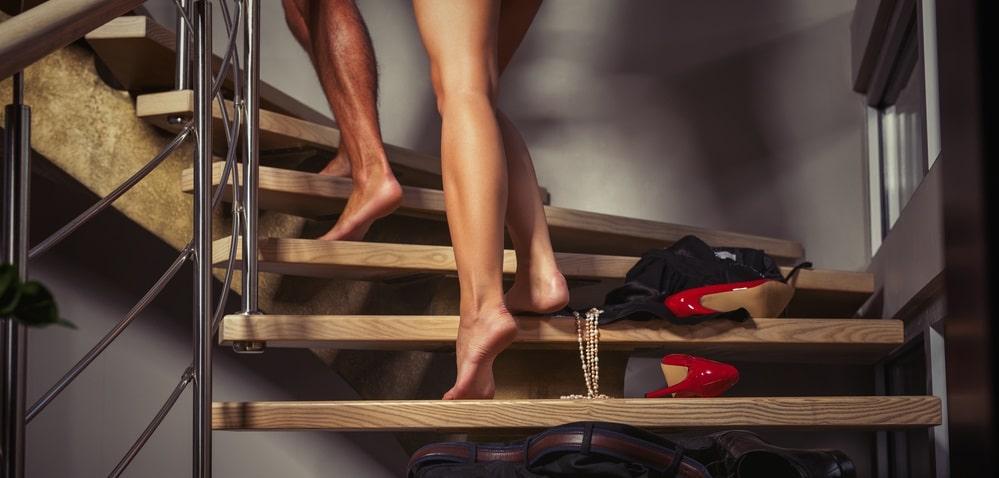 階段で服を脱ぐカップル