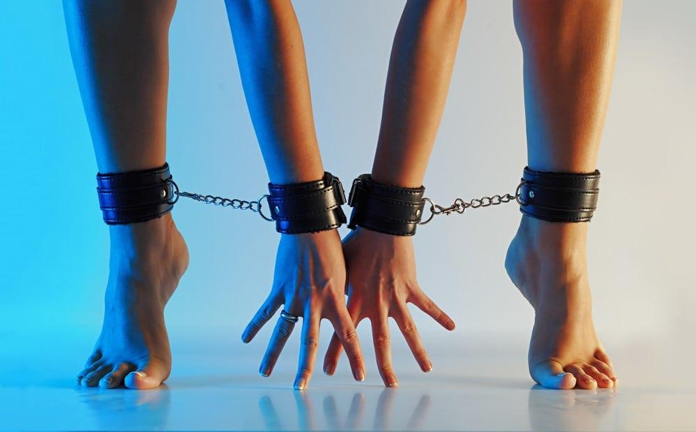 足枷と手錠プレイを楽しむ女性