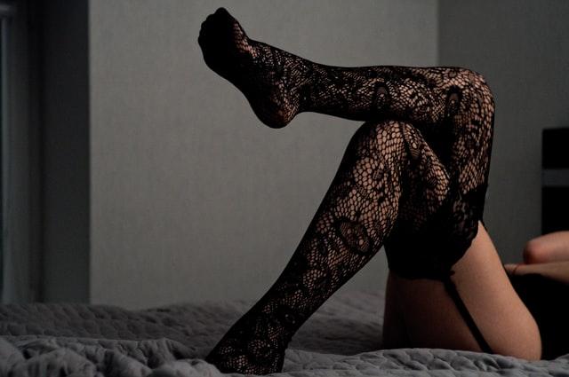黒ストッキングで足を組む女性の画像